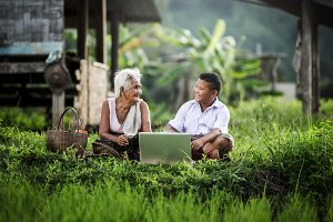 A boy and his grandmother collect data using a laptop in a lush and remote environment